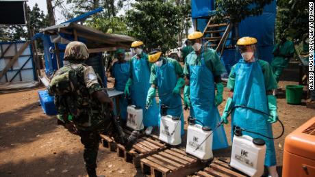 A UN peacekeeper has his shoes cleaned with a chlorine solution before leaving an Ebola treatment center in Mangina, North Kivu province, DRC, on September 1, 2019.