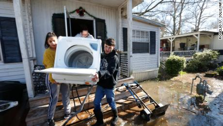 Alondra Rodriguez, left, her brother Mario Vargas and their aunt carry a washing machine from Vargas' mother's mobile home in Ridgeland, near Jackson, as the Pearl River rose Friday.