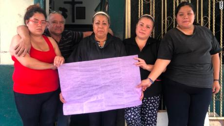 Nitzi Gonzalez and her family hold up purple tissue paper in support of victims of femicide.