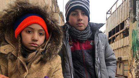 The kids wait patiently and without complaint outside their house in the last opposition-held territory in Syria, as their mother packs their belonging in the back of a truck.