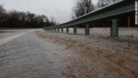 Water from the swollen Pearl River pushes under the guardrail along Old Brandon Road Bridge in Jackson, Mississippi, on Sunday.