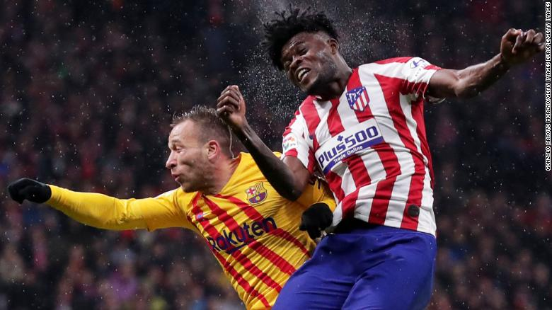 Thomas Partey of Atletico Madrid (R) and Arthur of FC Barcelona jump for the ball.