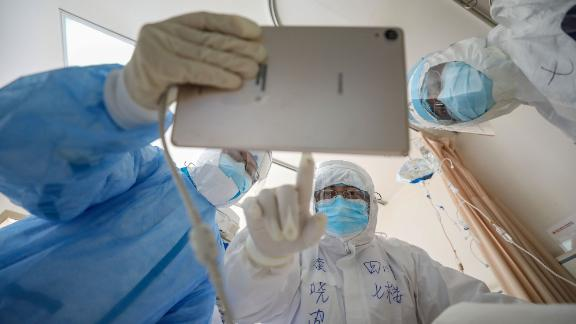 This photo taken on February 16, 2020 shows a doctor looking at an image as he checks a patient who is infected by the COVID-19 coronavirus at the Wuhan Red Cross Hospital in Wuhan in China's central Hubei province. - The death toll from the COVID-19 coronavirus epidemic jumped to 1,770 in China after 105 more people died, the National Health Commission said February 17. (Photo by STR / AFP) / China OUT (Photo by STR/AFP via Getty Images)