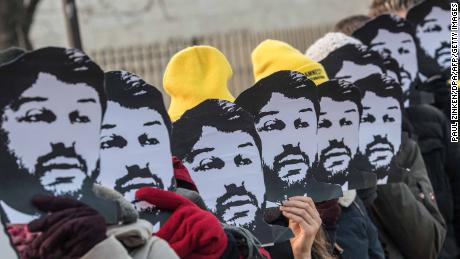 Amnesty International campaigners hold masks of Turkish rights activist Taner Kilic during a demonstration in Berlin in 2018.