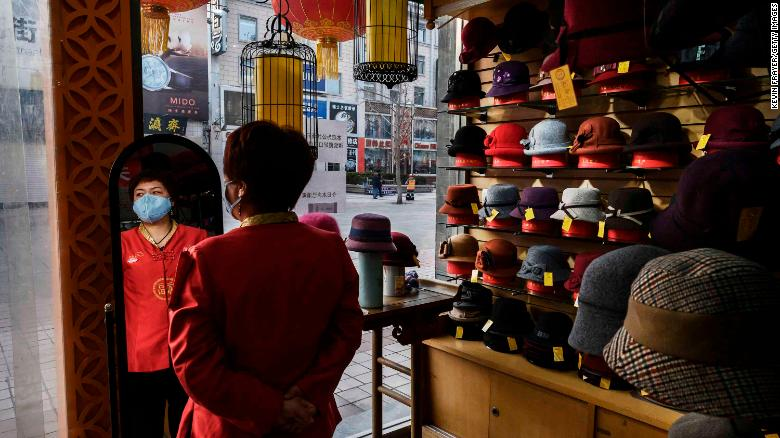 "A sales clerk wears a mask as she waits for customers at a hat shop in Beijing on Tuesday, February 18.<a href=""https://www.cnn.com/2020/02/14/economy/coronavirus-china-economy-small-businesses/index.html"" target=""_blank""> </a>Small companies that help drive China's economy <a href=""https://www.cnn.com/2020/02/14/economy/coronavirus-china-economy-small-businesses/index.html"" target=""_blank"">are worried about how much damage</a> the coronavirus outbreak will cause to business."