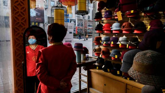 """A sales clerk wears a mask as she waits for customers at a hat shop in Beijing on February 18.<a href=""""https://www.cnn.com/2020/02/14/economy/coronavirus-china-economy-small-businesses/index.html"""" target=""""_blank""""> </a>Small companies that help drive China's economy <a href=""""https://www.cnn.com/2020/02/14/economy/coronavirus-china-economy-small-businesses/index.html"""" target=""""_blank"""">are worried about how much damage</a> the coronavirus outbreak will cause to business."""
