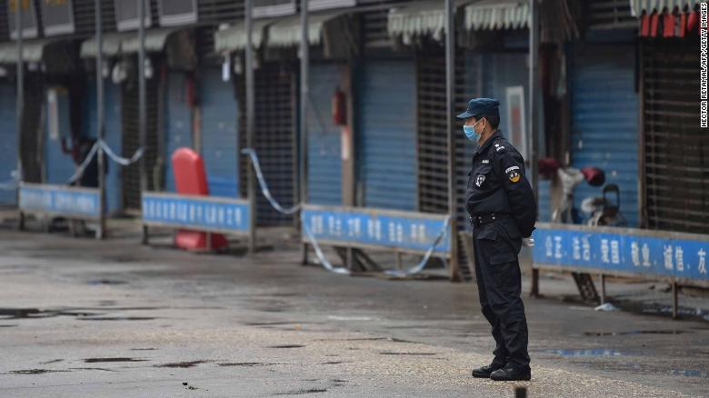A security guard stands outside the Huanan Seafood Wholesale Market where the coronavirus was detected in Wuhan on January 24.