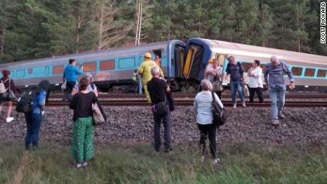 Passengers surround the derailed train.
