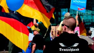 """Alternative for Germany (AfD)'s demonstrators holding AfD and German flags gather at the main station in Berlin to attend the """"demonstration for the future of Germany"""" called by the far-right AfD in Berlin on May 27, 2018. - The police estimates 2000 to 2500 people attending the AfD demonstration in front of the main station in Berlin. (Photo by Tobias SCHWARZ / AFP)        (Photo credit should read TOBIAS SCHWARZ/AFP via Getty Images)"""