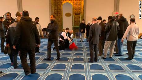 The suspect is seen being detained by police at mosque.