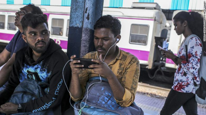 Passengers use smartphones while sitting on a platform of a railway station in Mumbai, India, on Saturday, Feb. 15, 2020.