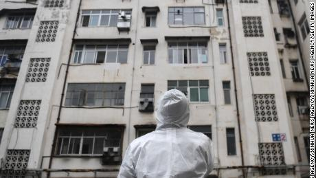 A community worker stands in front of a residential building as he prepares to conduct a health check in Caidian District of Wuhan.