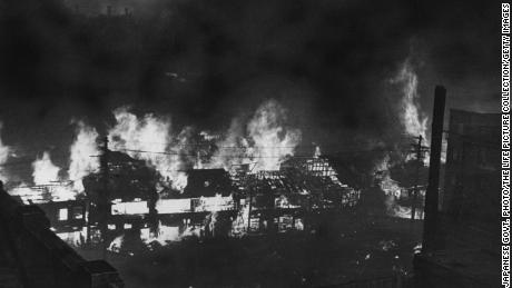 Japanese government photo shows buildings aflame after World War II firebomb raid.