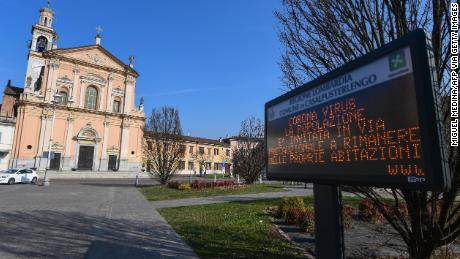 "A municipal information sign reads ""Coronavirus, the population is invited as a precautionary measure to remain at home"" is pictured in the village of Casalpusterlengo, southeast of Milan, on February 22, 2020. - Streets were deserted and residents warned to keep out of an emergency room on February 22, 2020 in the Italian town of Codogno placed under lockdown as a second death from coronavirus sparked fears throughout the region. (Photo by Miguel MEDINA / AFP) (Photo by MIGUEL MEDINA/AFP via Getty Images)"