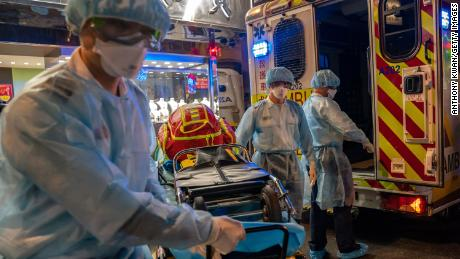 Paramedics wearing personal protective equipment carry a stretcher from an ambulance at North Point district in Hong Kong.
