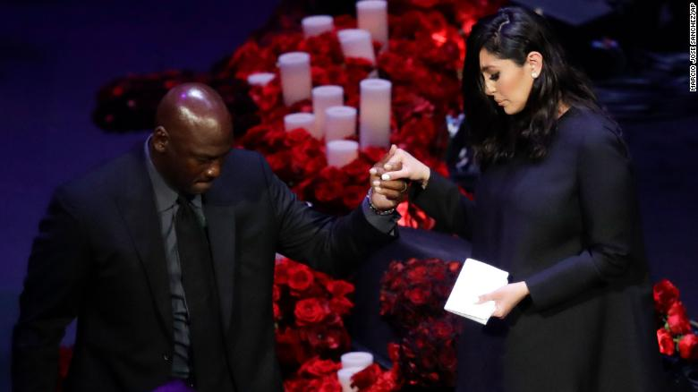 Vanessa Bryant is helped off the stage by former NBA player Michael Jordan.