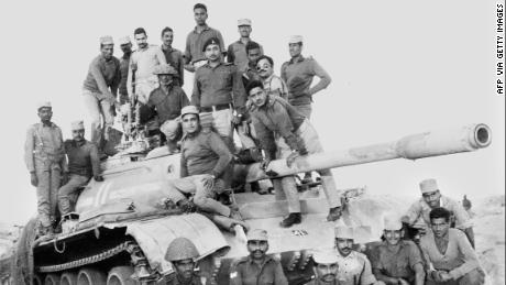 Indian army officers and soldiers on December 11, 1971, stand on a captured Pakistani tank in the desert of the state of Rajasthan during the India-Pakistan border conflict.