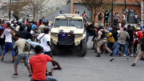 Armed off-duty police officers commandeer an armored vehicle during a protest over police pay and working conditions, in Port-au-Prince, Haiti, Sunday, Feb. 23, 2020.