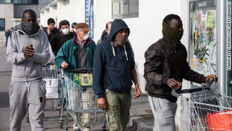 People wearing respiratory masks wait to get into a supermarket in Casalpusterlengo, southeast of Milan, on Sunday.