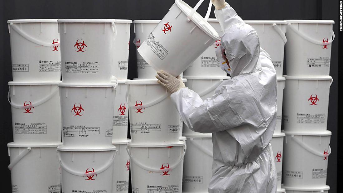 A worker in Daegu stacks plastic buckets containing medical waste from coronavirus patients on February 24.