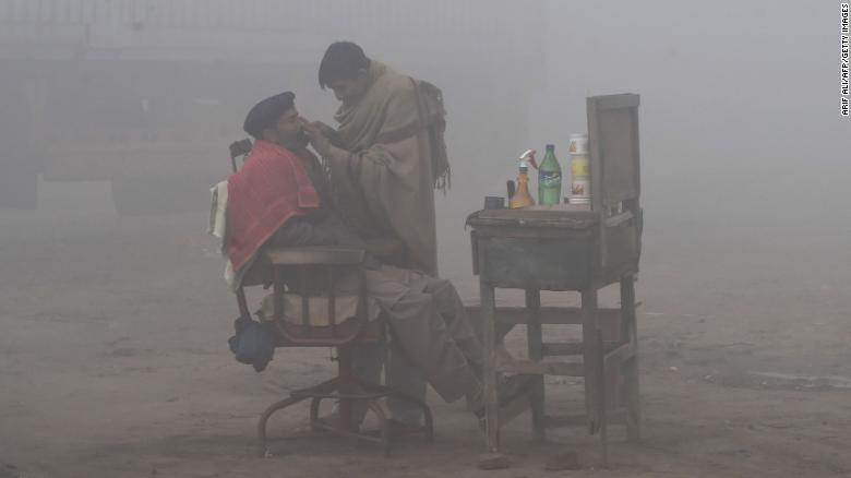 A Pakistani barber shaves a customer alongside a road amid heavy fog and smog conditions in Lahore.