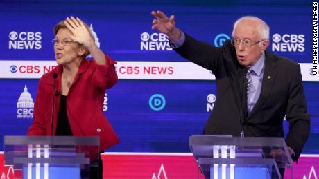 Democratic presidential candidates (L-R) Sen. Elizabeth Warren (D-MA) and Sen. Bernie Sanders (I-VT) raise their hands during the Democratic presidential primary debate at the Charleston Gaillard Center on February 25, 2020 in Charleston, South Carolina.