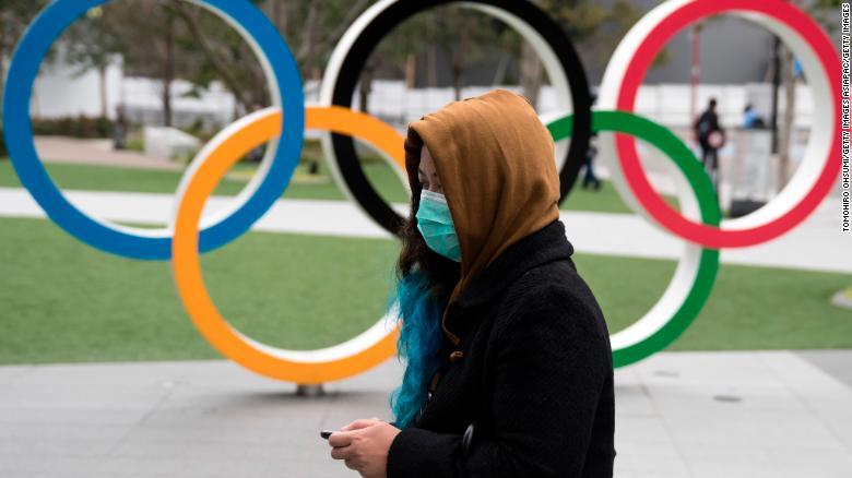 ผู้หญิงสวมหน้ากากเดินผ่านวงแหวนโอลิมปิกหน้าสนามกีฬาแห่งชาติใหม่ซึ่งเป็นสนามกีฬาหลักของโตเกียว 2020