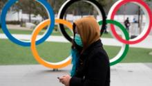 A woman wearing a face mask walks past the Olympic rings in front of the new National Stadium, the main stadium for Tokyo 2020.