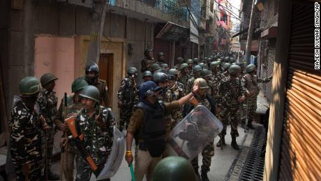 Indian paramilitary force soldiers ask people to go back in their houses after Tuesday's violence.