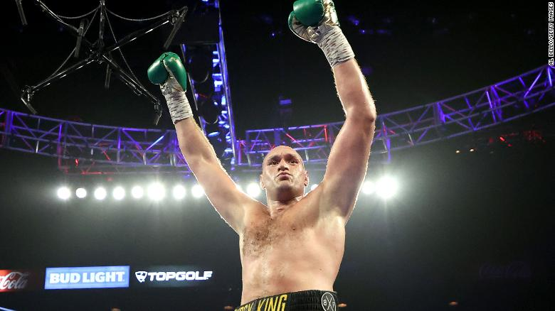 Fury celebrates after knocking down Deontay Wilder during their latest bout.