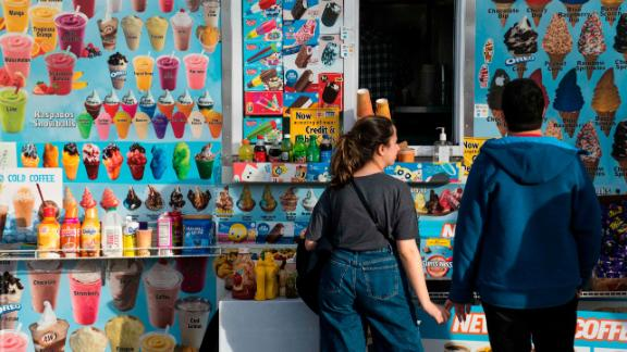 People buy ice cream from a truck in January in Washington. Up and down the east coast, residents are enjoying spring-like temperatures into the 60s in what should feel like winter.
