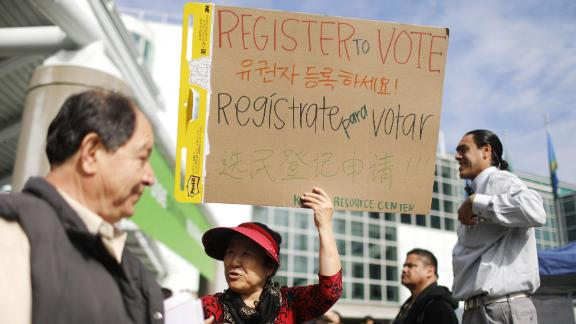 LOS ANGELES, CA - MARCH 20:  An election canvasser (C) holds a sign encouraging people to register to vote, written in various language, following a naturalization ceremony on March 20, 2018 in Los Angeles, California. The naturalization ceremony welcomed more than 7,200 immigrants from over 100 countries who took the citizenship oath and pledged allegiance to the American flag. During FY 2016, the United States welcomed 752,800 new citizens to the country.  (Photo by Mario Tama/Getty Images)