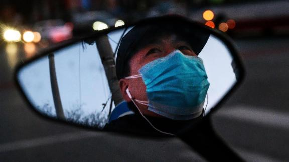 A Chinese man is seen in the side mirror of his scooter as he wears a protective mask while waiting at a red light in Beijing.