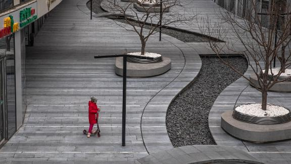 A child wearing a protective face mask rides on a scooter in an empty area in Beijing.