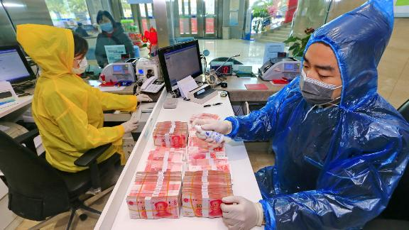 A bank clerk disinfects banknotes in China's Sichuan province on February 26.