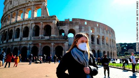 Tourist wearing a protective respiratory mask tours outside the Colosseo monument in downtown Rome on February 28.