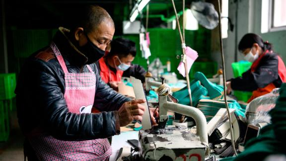 This photo taken on February 27, 2020 shows workers wearing face masks as they make insoles at the Zhejiang Xuda Shoes Co. factory in Wenzhou.