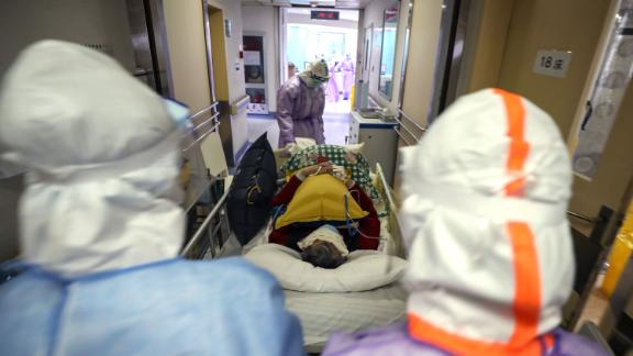 Medical staff transport a coronavirus patient within the Red Cross hospital in Wuhan on February 28.