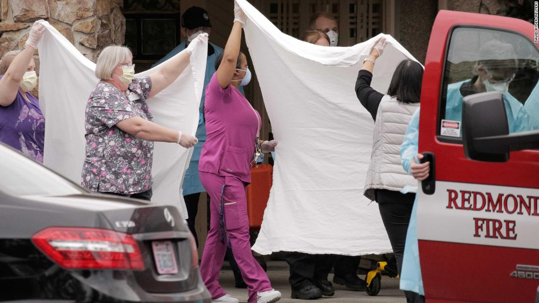 Health care workers transfer a patient at the Life Care Center in Kirkland, Washington, on March 1. The long-term care facility is linked to confirmed coronavirus cases.
