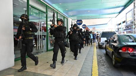 Members of a police SWAT team take positions outside one of the entrances to a mall after a hostage situation was reported in suburban Manila.