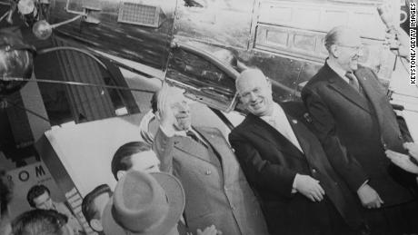 Nikita Khrushchev, center, who led the Soviet Union during the first part of the Cold War, stands in front of a model of Sputnik III.