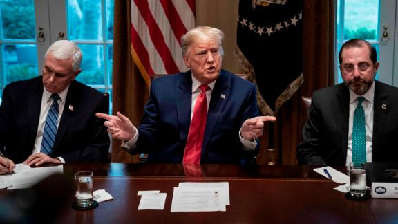 """US President Donald Trump, flanked by Vice President Mike Pence, left, and Health and Human Services Secretary Alex Azar, speaks during a meeting with pharmaceutical executives and the White House coronavirus task force on March 2. Throughout <a href=""""https://www.cnn.com/2020/03/02/politics/donald-trump-coronavirus-vaccine-push-back/index.html"""" target=""""_blank"""">the meeting,</a> Trump was hyperfocused on pressing industry leaders in the room for a timeline for a coronavirus vaccine and treatment. But experts at the table -- from the administration and the pharmaceutical industry -- repeatedly emphasized that a vaccine can't be rushed to market before it's been declared safe for the public."""