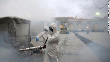 Members of the medical team spray disinfectant to sanitize outdoor place of Imam Reza's holy shrine in Mashhad, Iran on February 27.