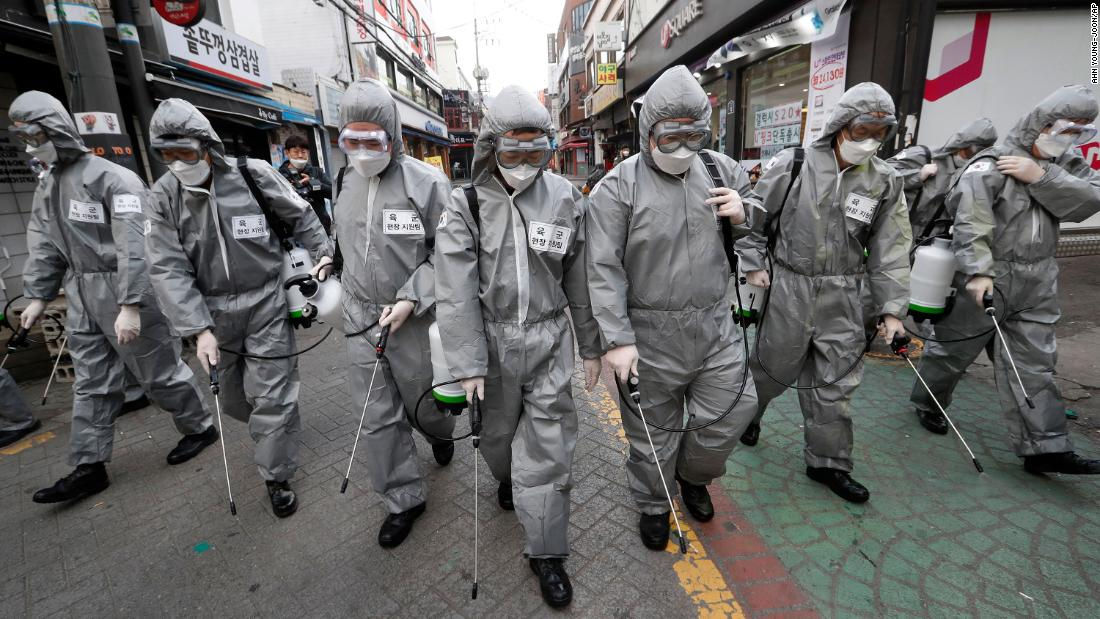 Soldiers spray disinfectant throughout a shopping street in Seoul.