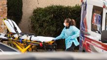 A healthcare worker prepares to transport a patient on a stretcher into an ambulance at Life Care Center of Kirkland on February 29.