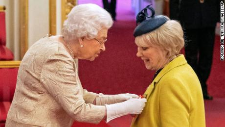 Queen Elizabeth wears gloves during an investiture ceremony at Buckingham Palace in London on Tuesday.
