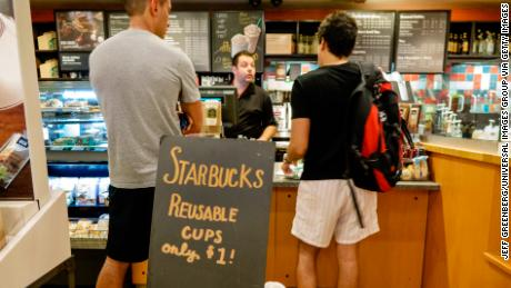 Interior of Starbucks Coffee with customers standing at the counter behind reusable cups sign.