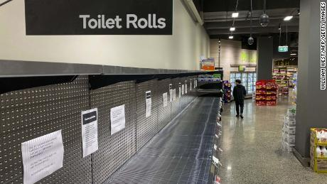 A shopper passes empty shelves usually stocked with toilet paper in a supermarket in Melbourne on March 5.