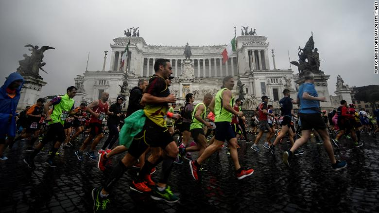 Competitors run past the Altare della Patria monument after taking the start of the 25th edition of Rome Marathon on April 7, 2019 in Rome.