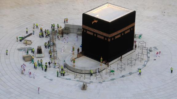 Municipal workers are seen at the Kaaba, inside Mecca's Grand Mosque. Saudi Arabia emptied Islam's holiest site for sterilization over coronavirus fears, an unprecedented move after the kingdom suspended the year-round Umrah pilgrimage.